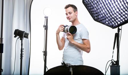 Fotógrafo profesional joven con cámara digital - DSLR y un gran teleobjetivo en su estudio bien equipado, tomando fotos (imagen en tonos de color; DOF superficial) Foto de archivo
