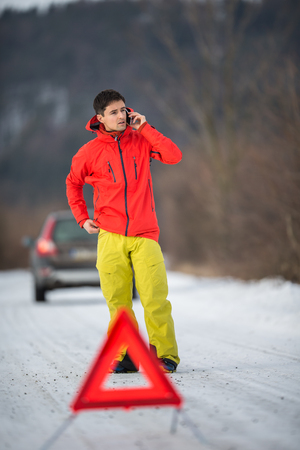 Young man setting up a warning triangle and calling for assistance after his car broke down in the middle of nowhere on a freezing winter day