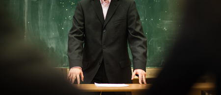 Teacher in a suit in front of a blackboard in a classroom