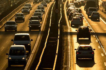 Concepto de tráfico / congestión de la ciudad por la mañana pesada: los automóviles van muy lentamente en un atasco durante la hora punta de la mañana