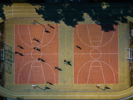 Aerial view of a soccer  pitch with people playing soccer on it - in warm morning sun, casting long shadows Stock Photo