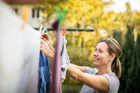 Young woman putting laundry on a rope in her garden,  taking great care of her family on a daily basis Фото со стока - 115347779