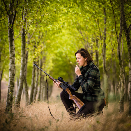 Autumn hunting season. Hunting. Outdoor sports. Woman hunter in the woods with her well trained dog Stock fotó