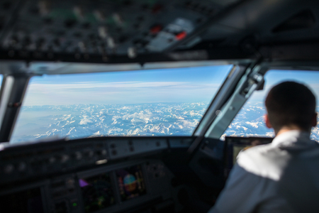 Pilot in  a commercial airliner airplane flight cockpit during flight with great weather