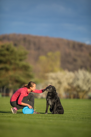 Young woman throwing freisbee to her black dog outdoors