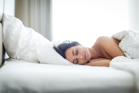 Beautiful young woman sleeping on bed at bedroom Imagens