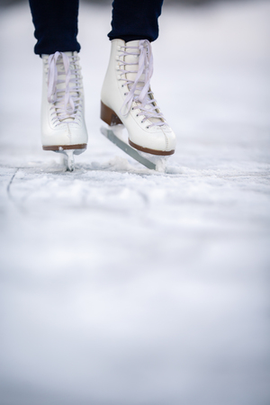 Young woman ice skating outdoors on a pond on a freezing winter day Stockfoto