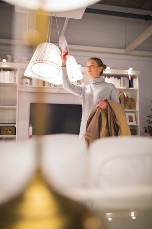 Pretty, young woman choosing the right lamp for her apartment in a modern home furnishings store (color toned image; shallow DOF) 版權商用圖片