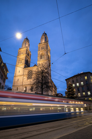 Zurich, Switzerland - view of the Grossmünster church with motion blurred tramway during Chrostmas time