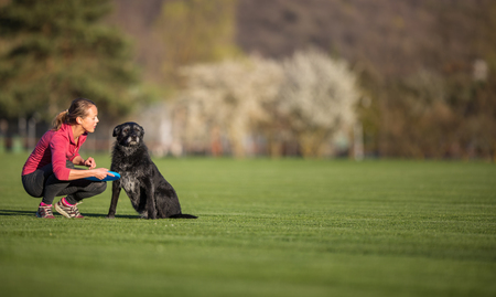Young woman with her black dog  outdoor, in a park playing frisbee - shallow DOF, sharp focus Stock Photo