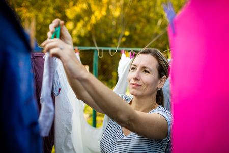 Young woman putting laundry on a rope in her garden,  taking great care of her family on a daily basis Фото со стока - 115348692