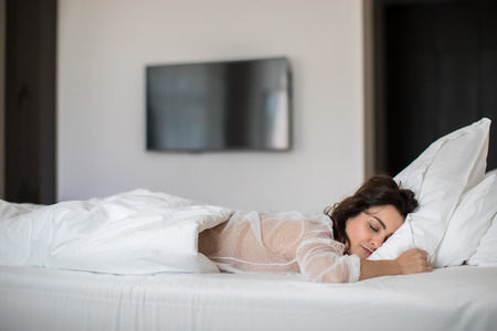 Beautiful young woman sleeping on bed at bedroom 写真素材