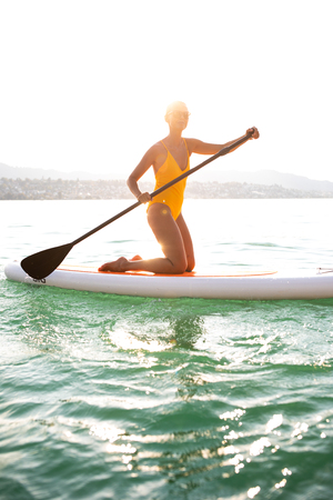 SUP Stand up paddle board concept - Pretty, young woman paddle boarding on a lovely lake in warm late afternoon light Standard-Bild