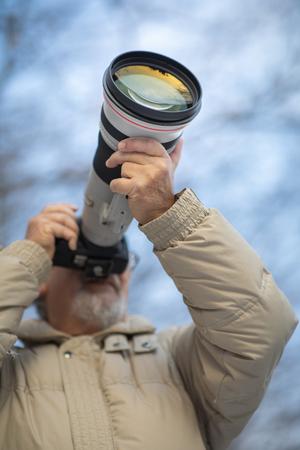 Hombre senior dedicando tiempo a su pasatiempo favorito, la fotografía, tomando fotos al aire libre con su cámara digital / DSLR y un gran teleobjetivo