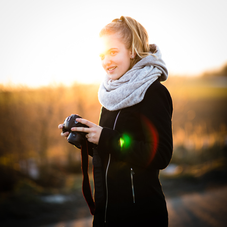Cute female photographer with her dslr camera taking photos outdoor at sunset - photography taking concept (color toned image)