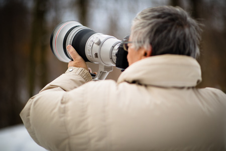 Senior man devoting time to his favorite hobby - photography - taking photos outdoor with his digital cameraDSLR and a big telephoto lens Stock Photo