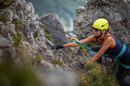 Pretty, female climber on a via ferrata - climbing on a rock in Swiss Alps 스톡 콘텐츠