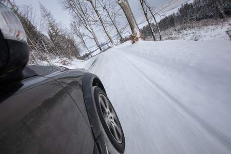 Fast moving car on a winter alpine snowy road