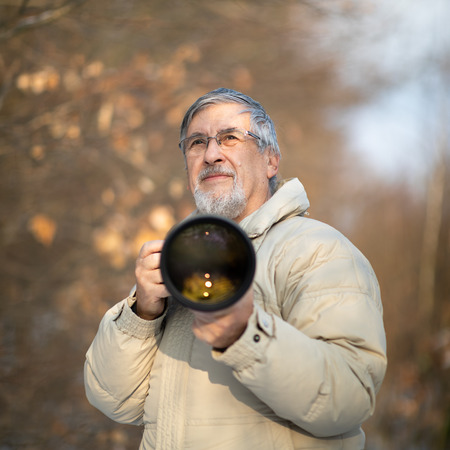 Senior man devoting time to his favorite hobby - photography - taking photos outdoor with his digital camera/DSLR and a big telephoto lens