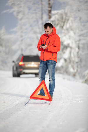 Handsome man setting up a warning triangle and calling for assistance after his car broke down in the middle of nowhere on a freezing winter day