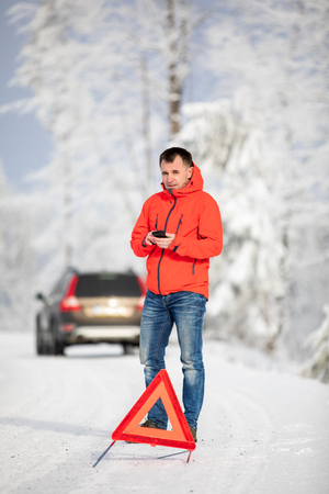 Handsome man setting up a warning triangle and calling for assistance after his car broke down in the middle of nowhere on a freezing winter day Stock Photo - 117810028