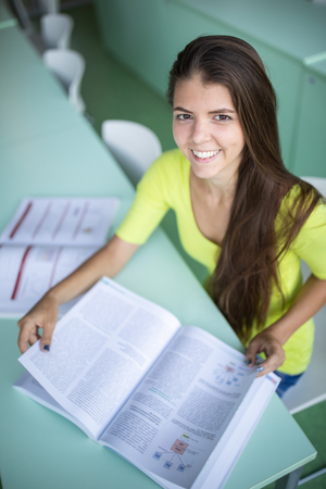 Cute female university/highschool student with books in library