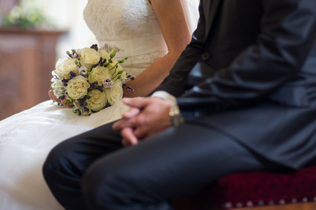 Wedding bouquet in the bride's hand on her wedding day (color toned image; shallow DOF)