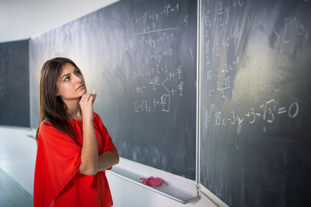 Pretty, young college student writing on the chalkboardblackboard during a math class Stock Photo