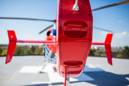 Modern medical helicopter on a hospital rooftop helipad from behind - shallow DOF Stock Photo