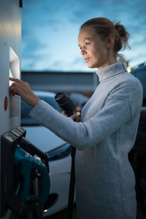Young woman charging an electric vehicle. Car sharing concept.