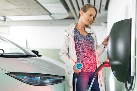 Jeune femme chargeant un véhicule électrique dans un garage souterrain équipé d'un chargeur de voiture électrique. Concept de partage de voiture.