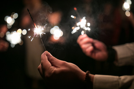 Wedding guests during the evening wedding ceremony holding sparklers Stock Photo