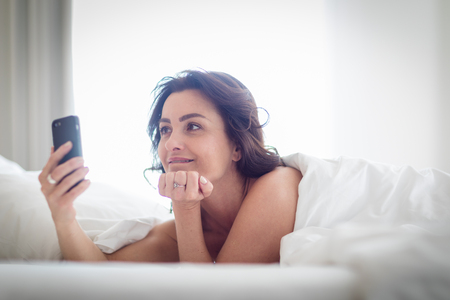 Beautiful young woman using her cell phone in bed on a lovely morning