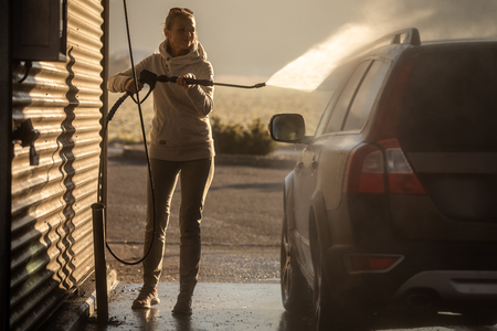 Cute woman washing her car in a manual carwash (color toned image)