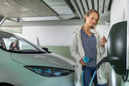 Junge Frau, die ein Elektrofahrzeug in einer Tiefgarage auflädt, die mit einem E-Auto-Ladegerät ausgestattet ist. Carsharing-Konzept.