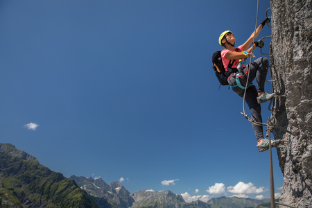 Pretty, female climber on a via ferrata - climbing on a rock in Swiss Alps Фото со стока
