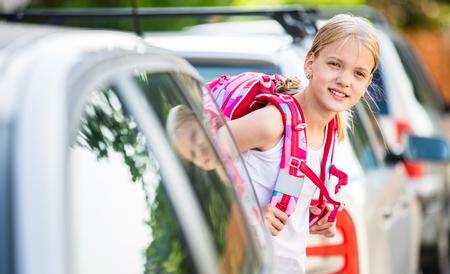 Jolie petite fille rentrant de l'école, en regardant bien avant de traverser la rue