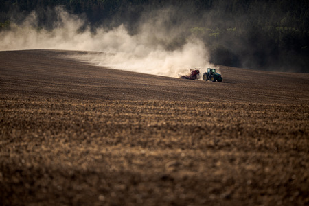 Tractor plowing a dry farm field - acute drought the soil suffers from being quite obvious from the amount of dust