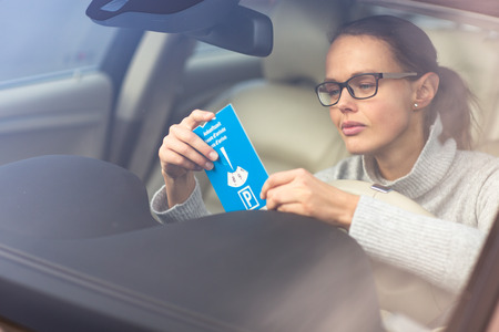 Pretty, young woman driving her new car - putting the necessary parking clock behind the windshield(color toned image; shallow DOF) Stockfoto