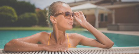 Young Beautiful Suntanned Woman wearing sunglasses relaxing next to a Swimming Pool  on a lovely Summer Day 版權商用圖片