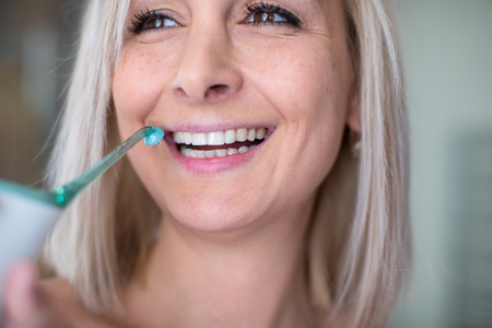 Pretty, middle aged woman brushing her teeth in a modern design bathroom - using the tooth shower instead of dental floss and looking very happy about not having to floss anylonger