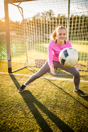 Teen female goalie catching a shot during a soccer game