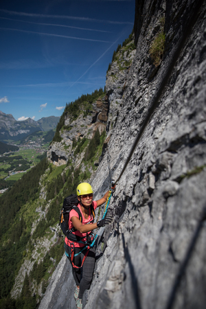 Pretty, female climber on a via ferrata - climbing on a rock in Swiss Alps 写真素材