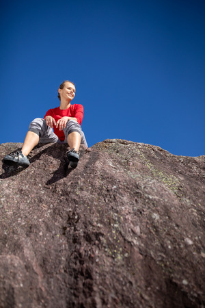 Young female climber atop a natural boulder outdoors, in Swiss Alps