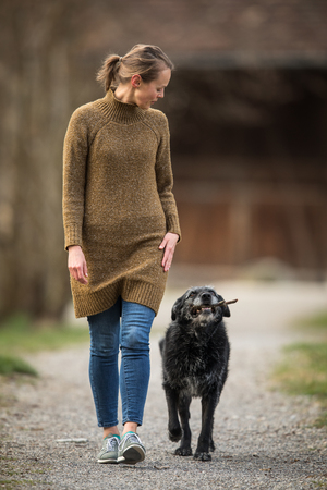 Young woman walking her dog after work in a park Stock Photo