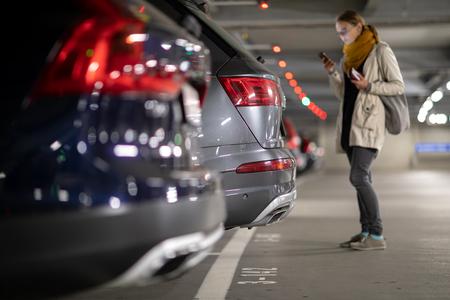 Garaje subterráneo o estacionamiento moderno con muchos vehículos, perspectiva de la fila de autos con una conductora buscando su vehículo Foto de archivo
