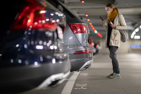 Underground garage or modern car parking with lots of vehicles, perspective of the row of the cars with a female driver looking for her vehicle Banco de Imagens