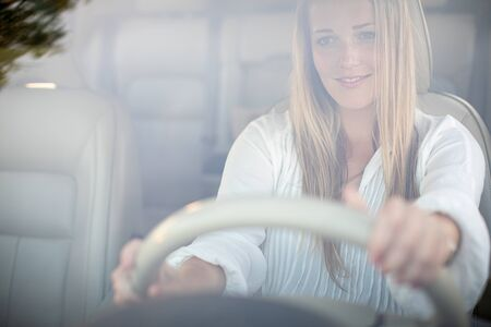 Pretty, young woman  driving a car -Invitation to travel. Car rental or vacation. Stockfoto