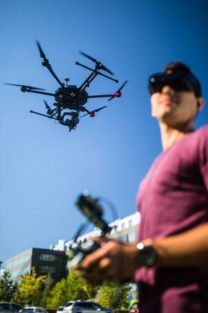 Handsome young man flying a drone outdoors using a VR/augmented reality glasses to operate the device, to see in real time the video feed from the drone