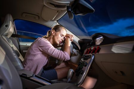 Young female driver at the wheel of her car, super tired, falling asleep while driving in a potentially dangerous situation - Road safety concept
